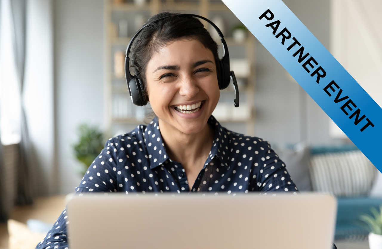 Lachende Frau mit Headset vor einem Laptop
