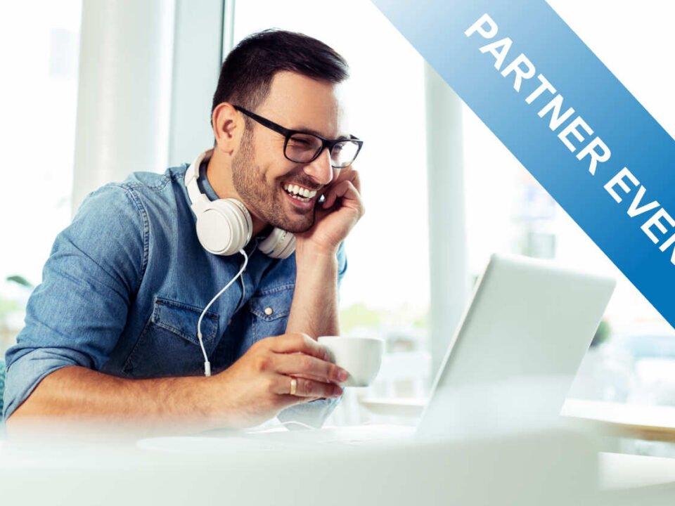 lachender Mann mit Kopfhörern vor einem Laptop