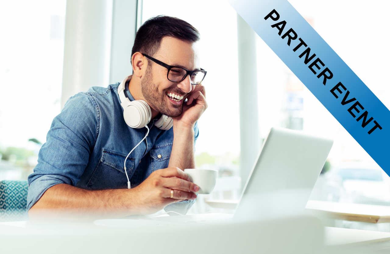 Lachender Mann mit Kopfhörern vor Laptop