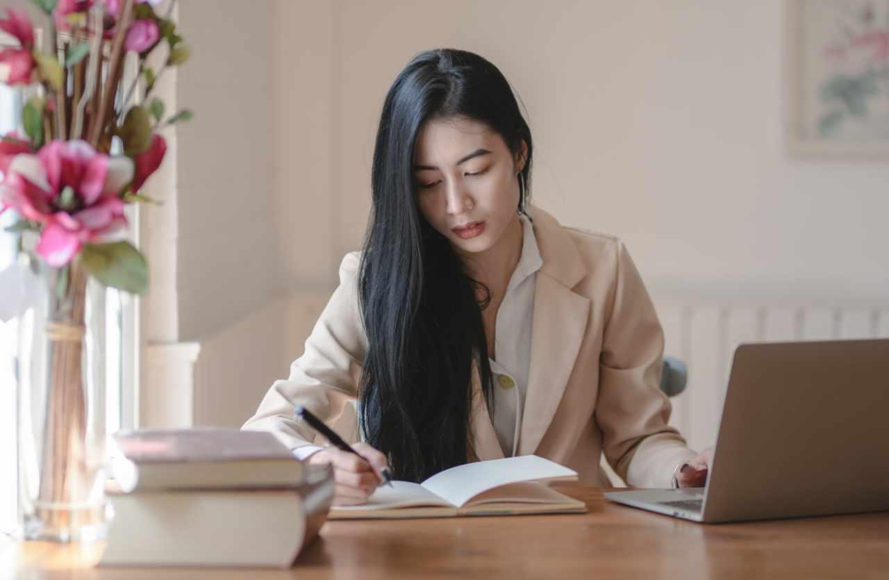 Asiatin sitzt am Schreibtisch
