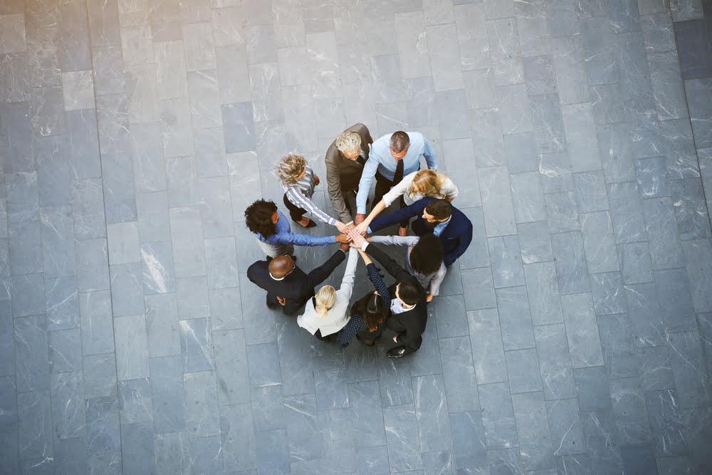 Gruppe von Menschen strecken Hände zusammen