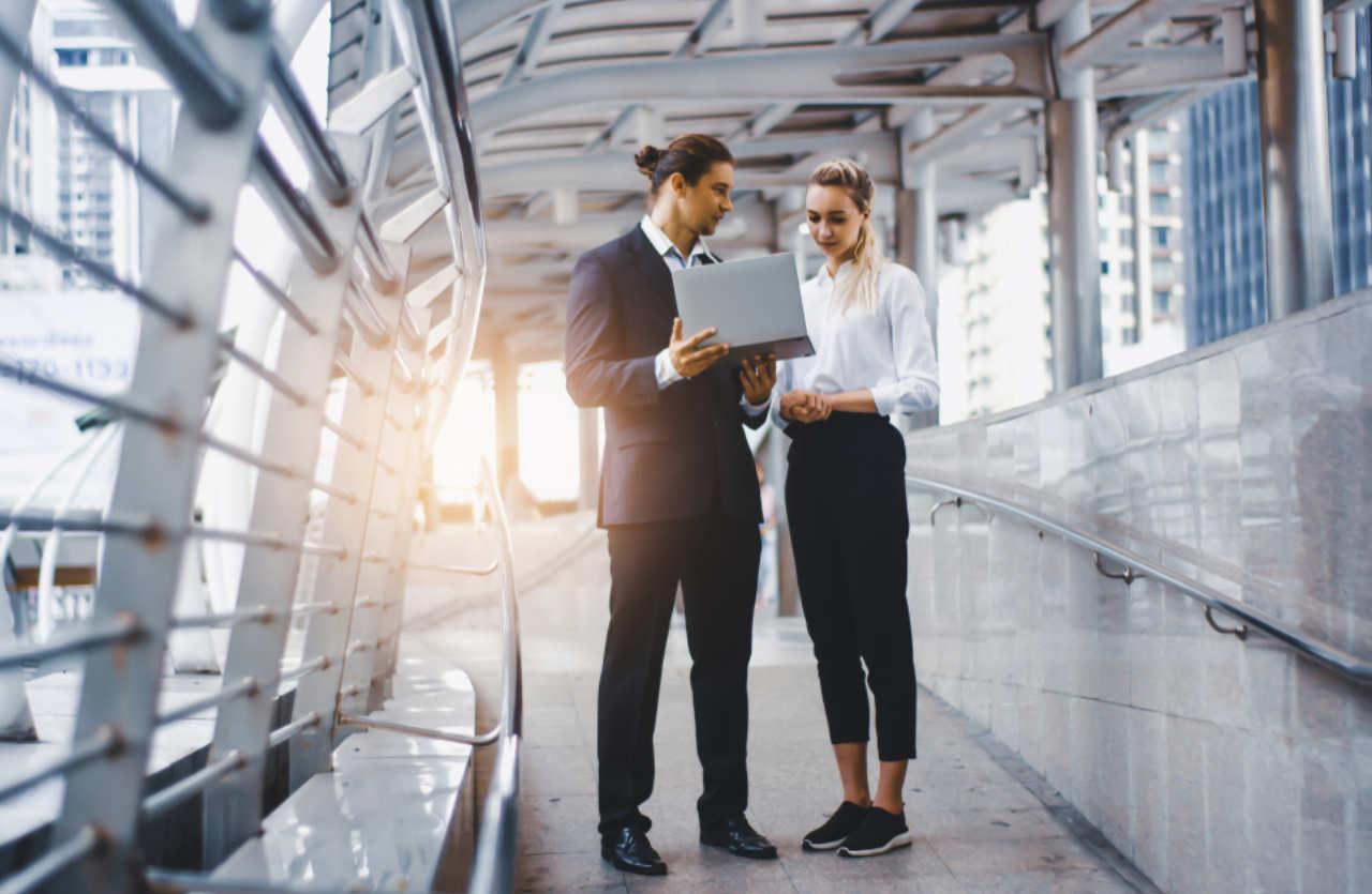 Mann und Frau stehen auf Brücke und schauen in Laptop